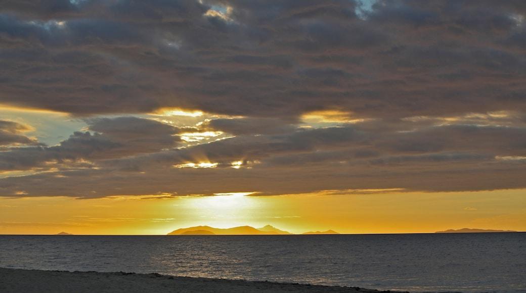 Beachcomber Island featuring a sandy beach, a sunset and landscape views