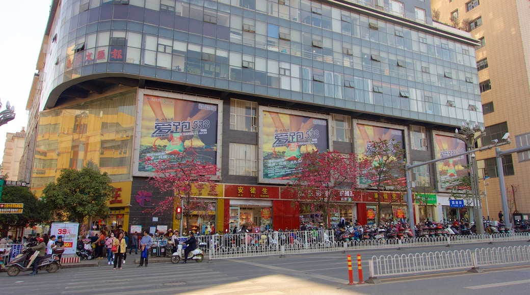 Kunming showing a city and signage as well as a small group of people