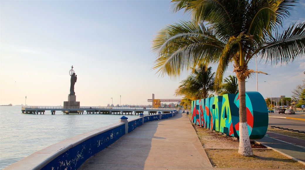 Ciudad del Carmen que incluye una estatua o escultura, un atardecer y señalización