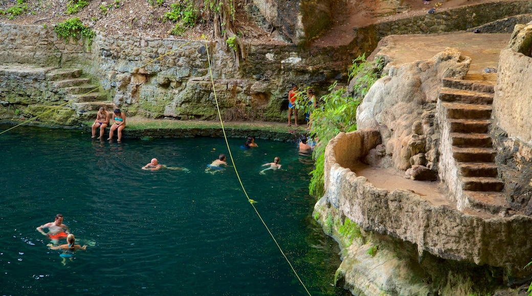 Cenote Zaci showing swimming and a lake or waterhole as well as a small group of people