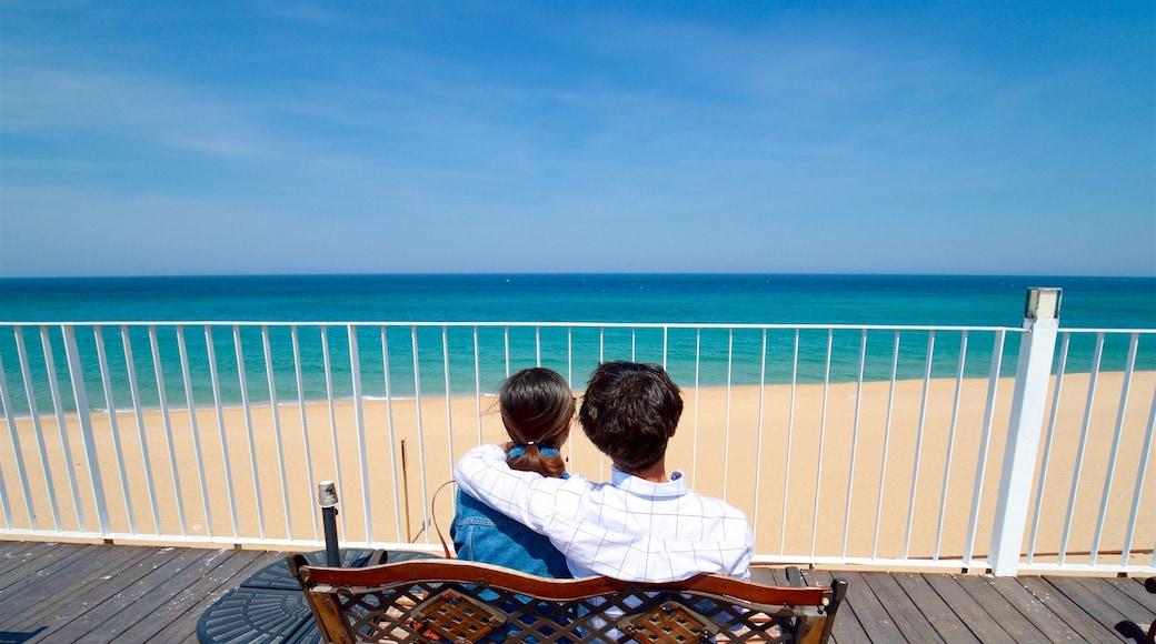 Jeongdongjin Beach featuring general coastal views and a sandy beach as well as a couple