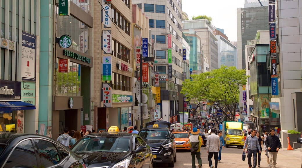 Myeongdong showing a city and central business district as well as a small group of people