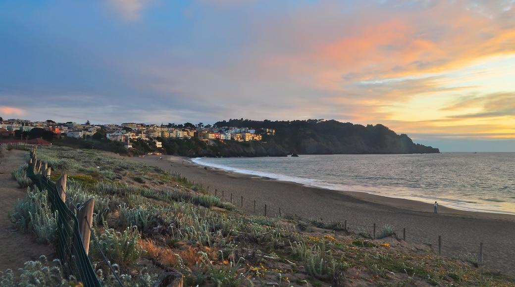 Baker Beach featuring a sunset, general coastal views and a beach