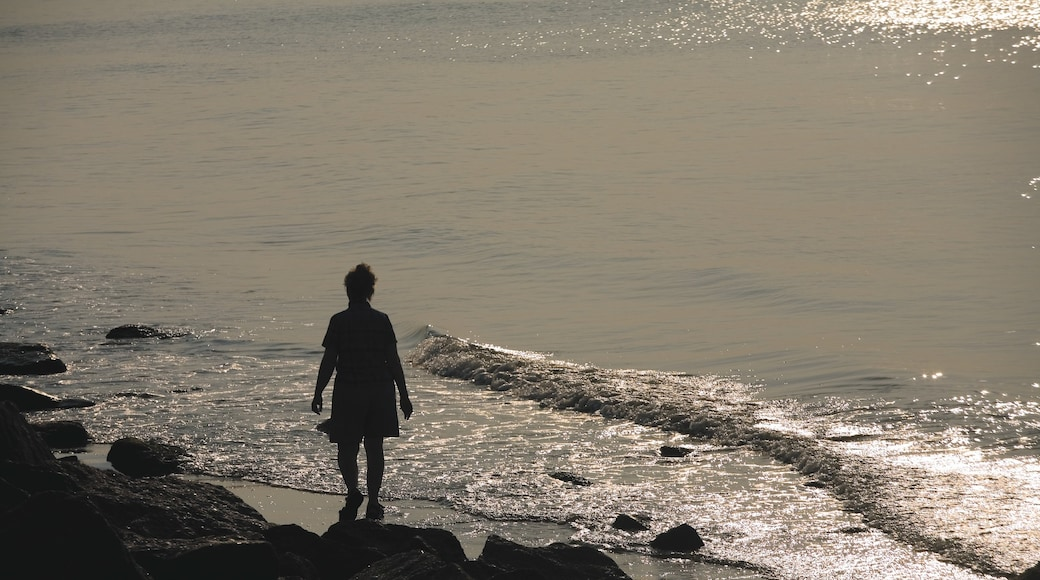 Galveston featuring a sunset, a beach and a pebble beach