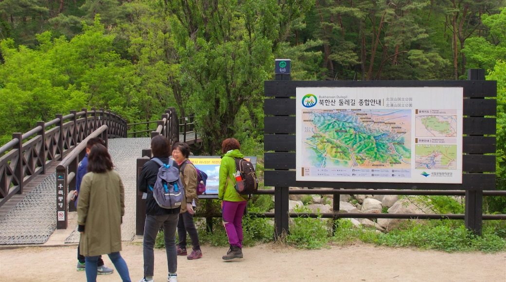 Bukhansan National Park showing forest scenes and signage as well as a small group of people