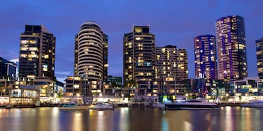 Docklands which includes a bay or harbour, night scenes and a high-rise building