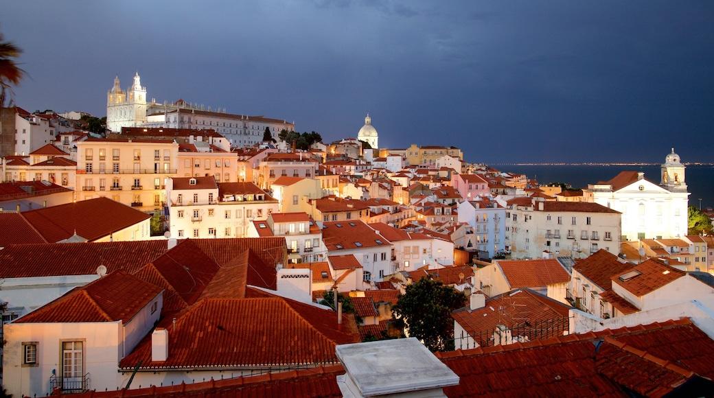 Miradouro de Santa Luzia showing a city, night scenes and a coastal town