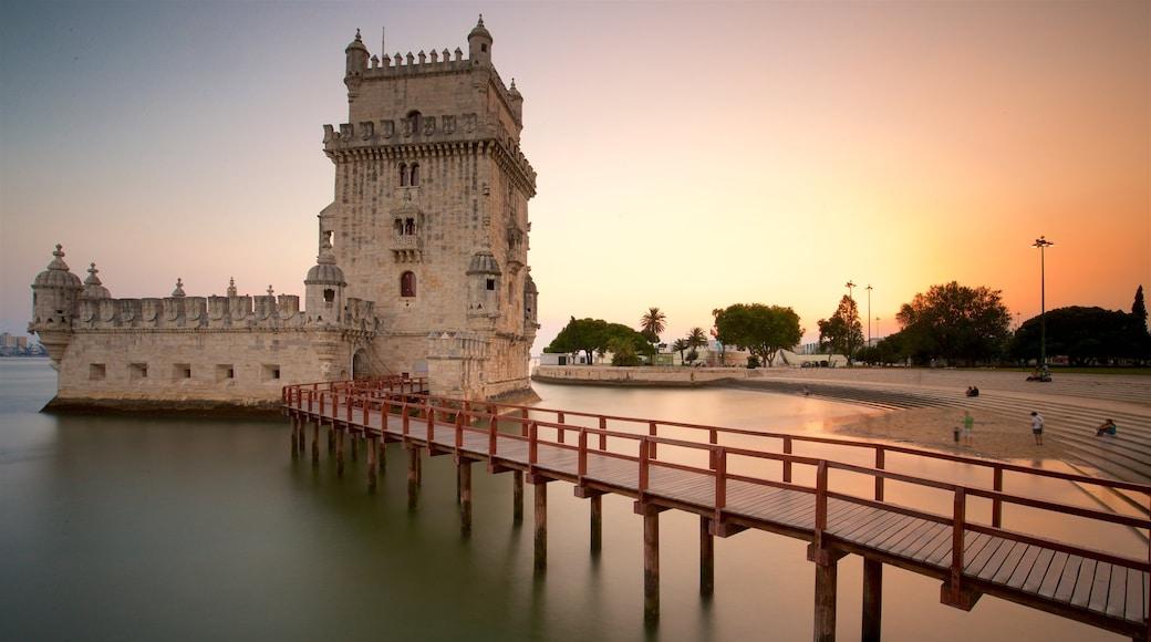 Torre de Belém que inclui uma ponte, paisagens litorâneas e um pôr do sol