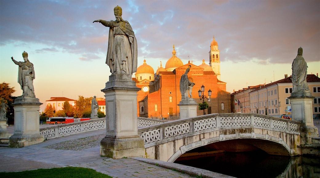 Prato della Valle which includes a statue or sculpture, a bridge and heritage architecture
