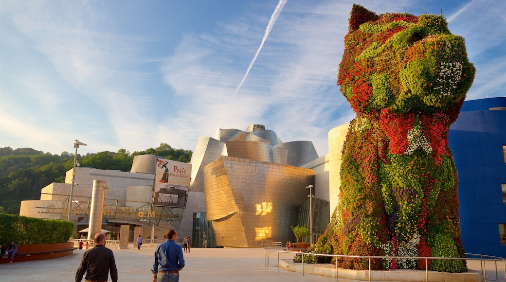 Museo Guggenheim Bilbao mostrando un atardecer, arquitectura moderna y escenas cotidianas