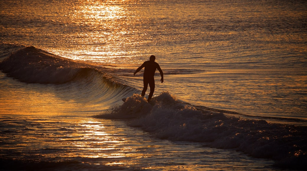 Coolangatta Beach showing a sunset, surf and surfing