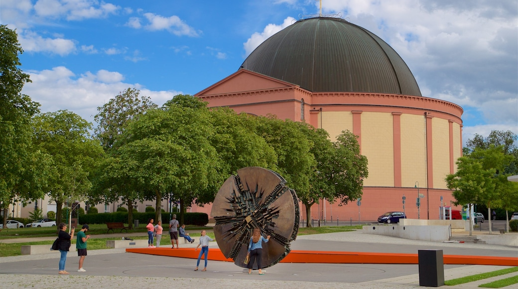 Darmstadt featuring a garden and outdoor art as well as a small group of people