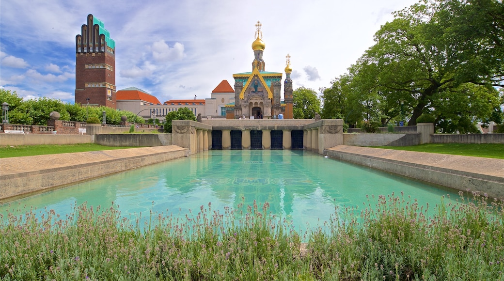 Russian Chapel featuring heritage architecture, a pond and wild flowers