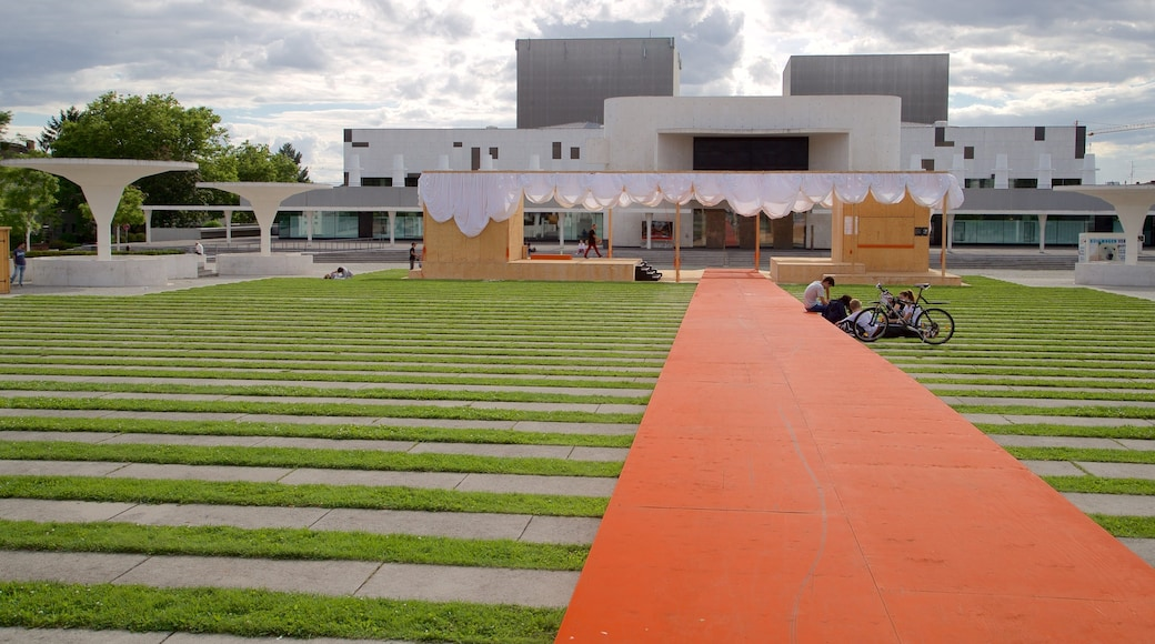 Darmstadt State Theatre showing modern architecture and a park as well as a small group of people