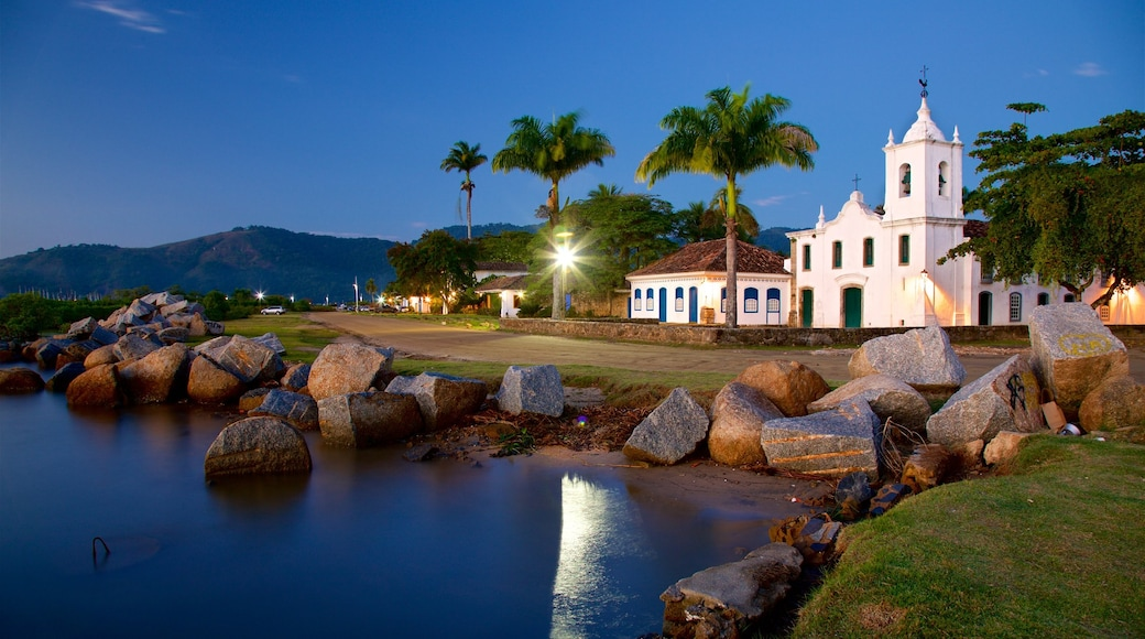 Nossa Senhora das Dores Church which includes a lake or waterhole, night scenes and a small town or village