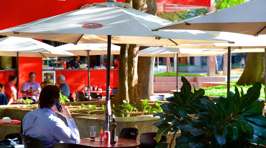 Praça da Savassi que inclui jantar ao ar livre assim como um homem sozinho