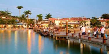 Buzios featuring a coastal town and general coastal views as well as a small group of people