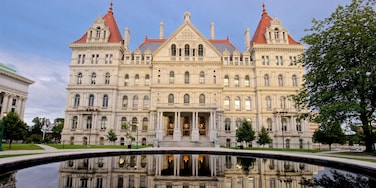 New York State Capitol Building featuring heritage architecture and a pond