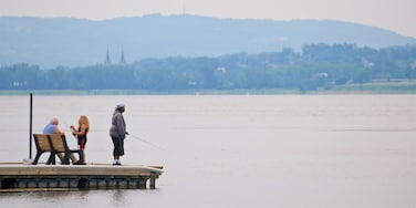 Onondaga Lake Park featuring fishing and a lake or waterhole as well as a small group of people