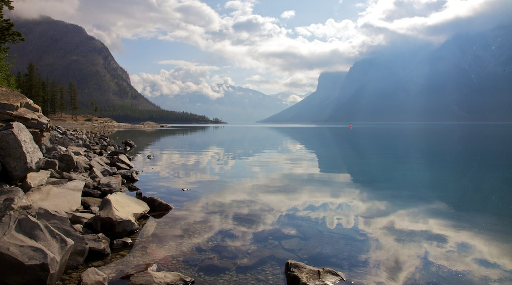 Lake Minnewanka which includes mountains, a lake or waterhole and landscape views