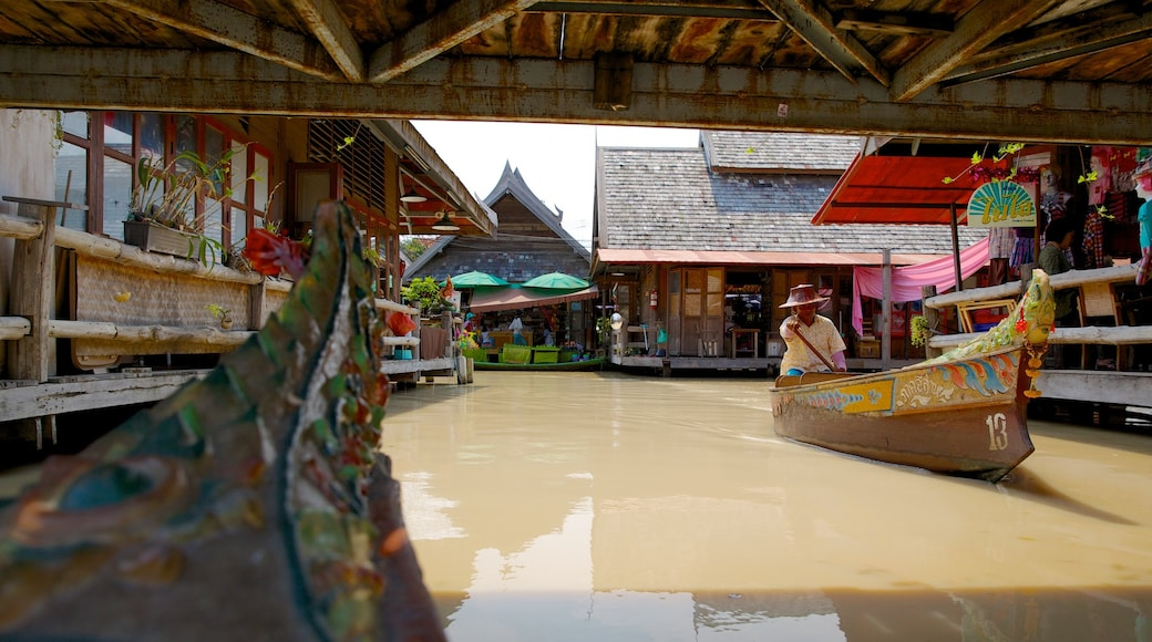 Pattaya Floating Market which includes a river or creek and markets as well as an individual male