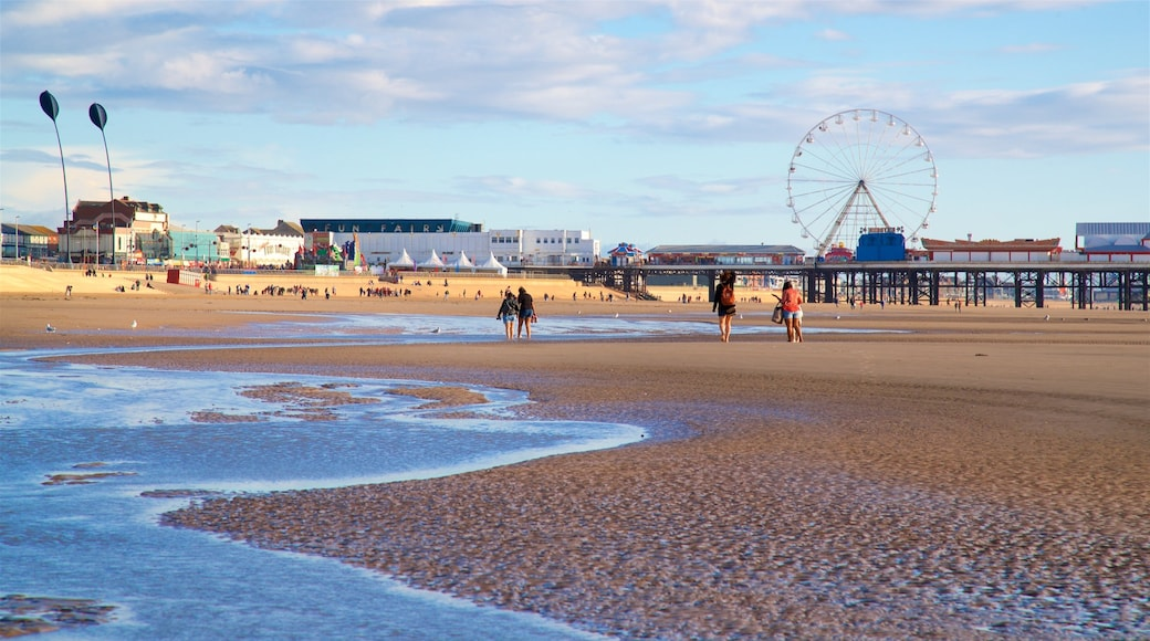 Blackpool Central Pier which includes a sandy beach and general coastal views as well as a small group of people