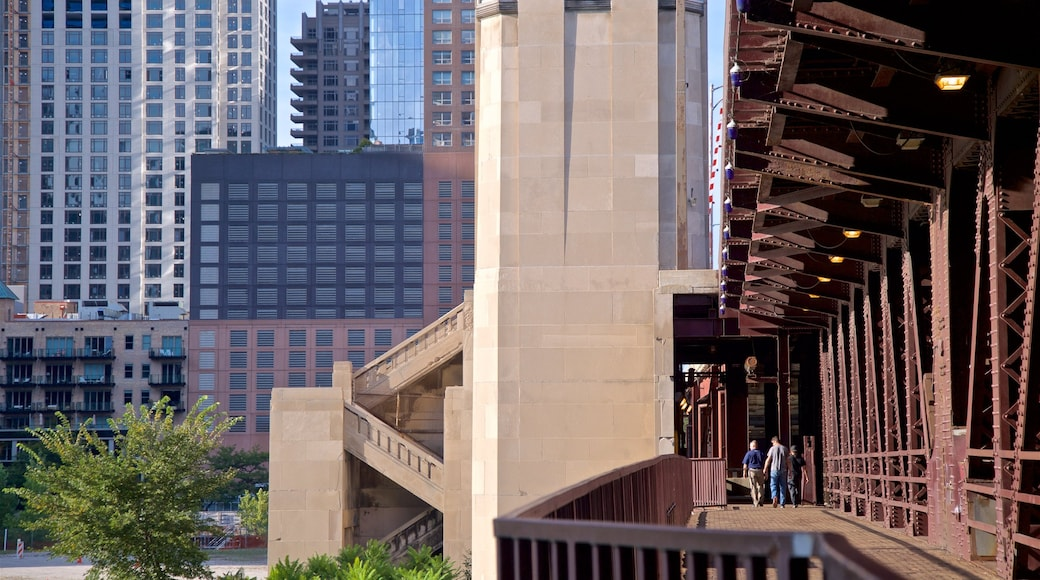 Chicago Riverwalk featuring a bridge and a city as well as a small group of people