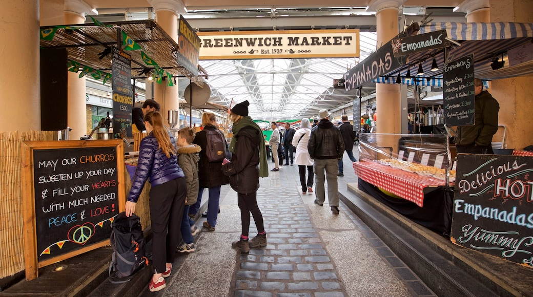 Greenwich Market showing markets and signage as well as a small group of people