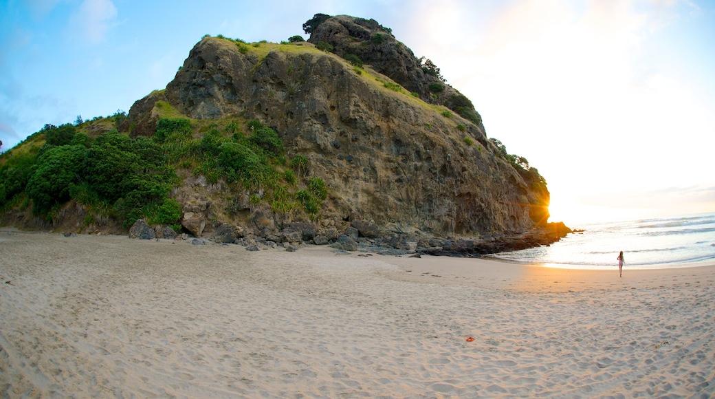 Piha Beach which includes a sunset, a beach and landscape views
