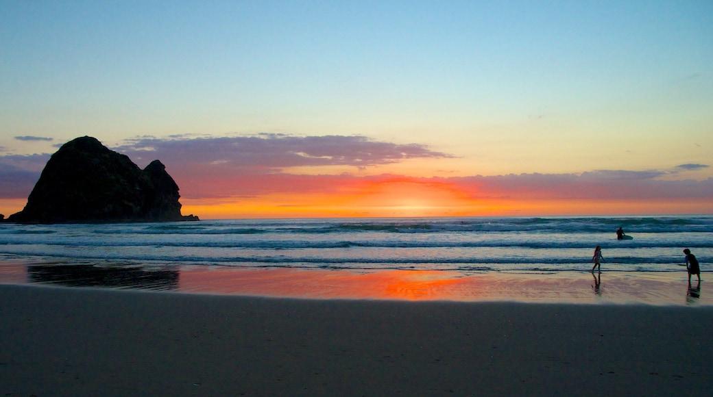 Piha Beach which includes landscape views, a sandy beach and a sunset