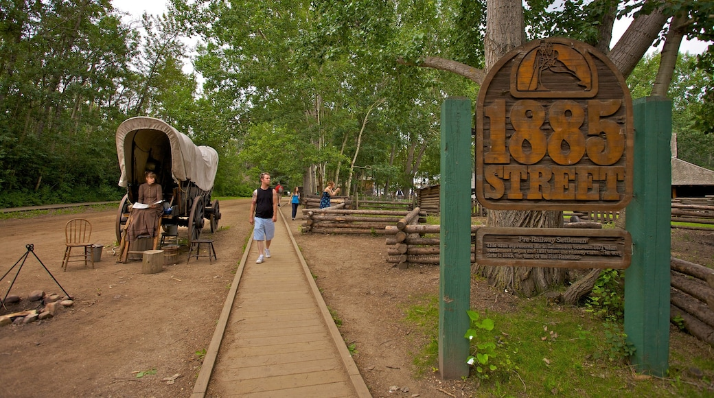 Fort Edmonton Park featuring signage and a park as well as an individual male