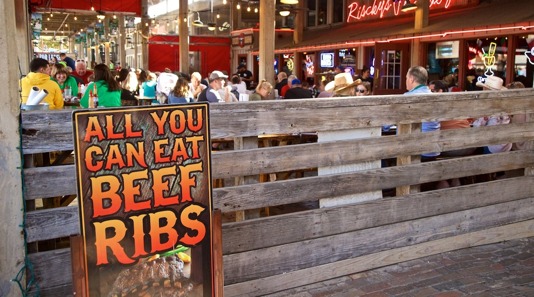 Fort Worth Stockyards which includes signage and outdoor eating as well as a small group of people