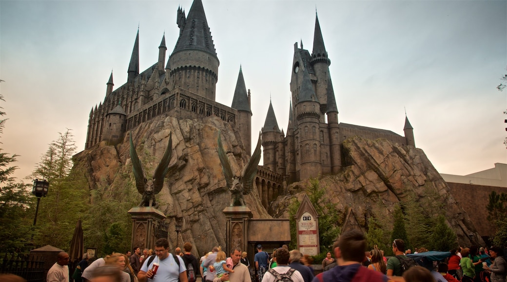 Parque temático The Wizarding World of Harry Potter™ mostrando un atardecer y atracciones y también un grupo pequeño de personas
