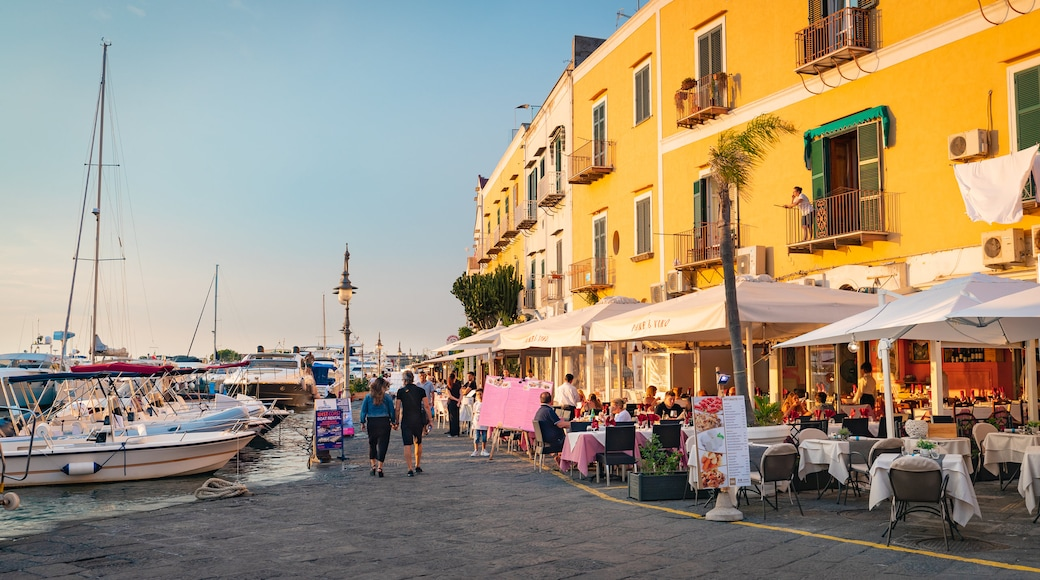 Ischia Port showing a bay or harbor, outdoor eating and a sunset