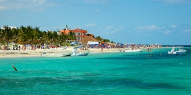 Puerto Morelos which includes a coastal town, tropical scenes and boating