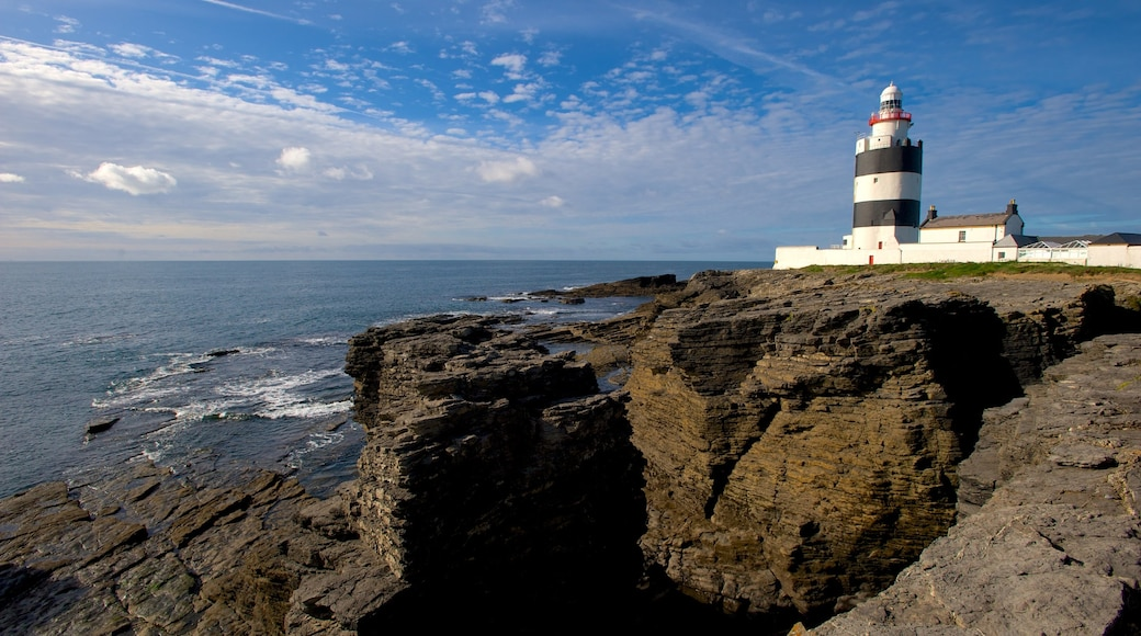 Ireland featuring rugged coastline, a lighthouse and landscape views