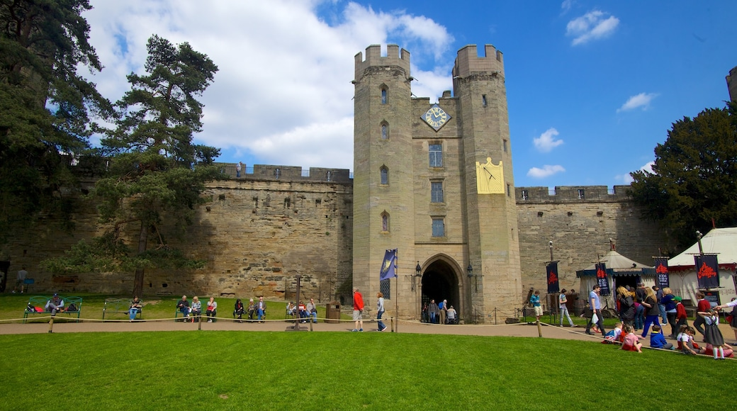 Warwick Castle which includes heritage architecture and château or palace as well as a large group of people