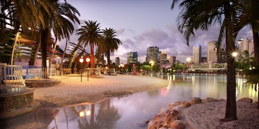 Southbank Parklands which includes tropical scenes, a sandy beach and night scenes