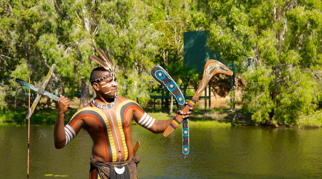 Tjapukai Aboriginal Cultural Park showing a park and a lake or waterhole as well as an individual male