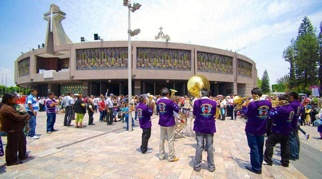 Basilica of Our Lady of Guadalupe showing street performance, religious elements and a church or cathedral