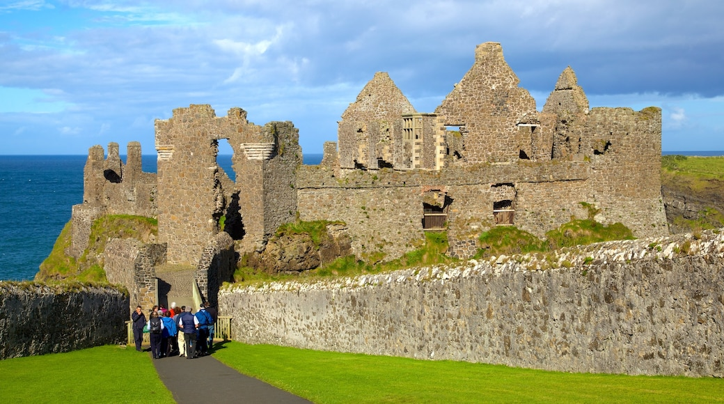 Dunluce Castle which includes heritage elements and a ruin as well as a small group of people
