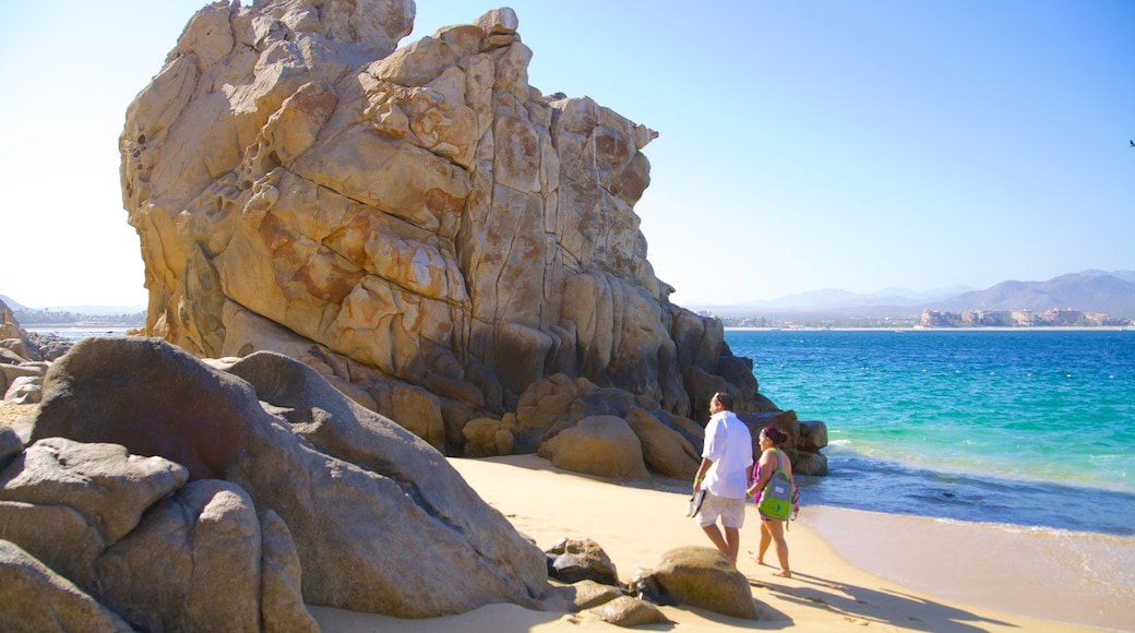 Playa del Amor showing rugged coastline and a beach as well as a couple