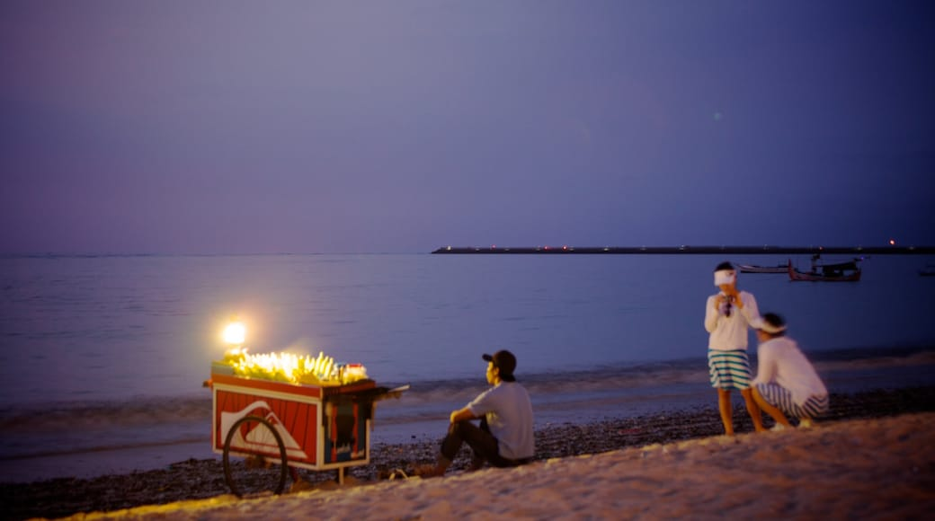 Jimbaran Beach showing night scenes and a sandy beach as well as a small group of people