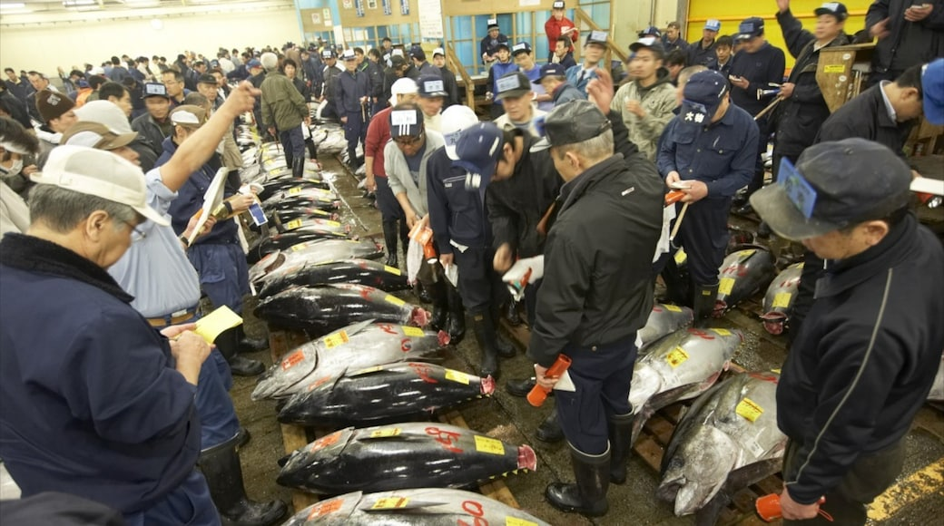 Tsukiji Fish Market which includes markets and interior views as well as a large group of people