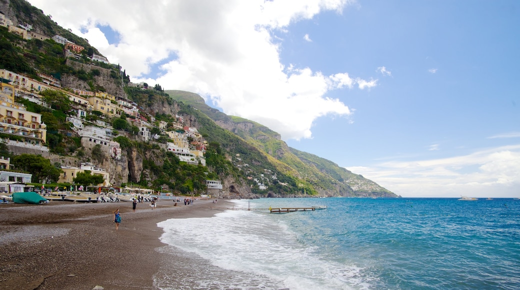 Positano which includes a coastal town, mountains and a sandy beach