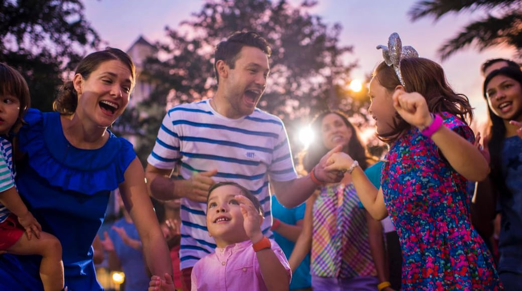 Disney Springs® showing a sunset as well as a family