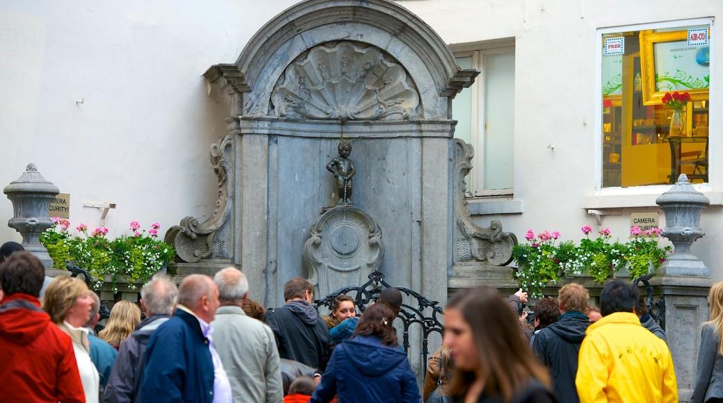 Manneken Pis mostrando monumento e statua o scultura cosi come un grande gruppo di persone