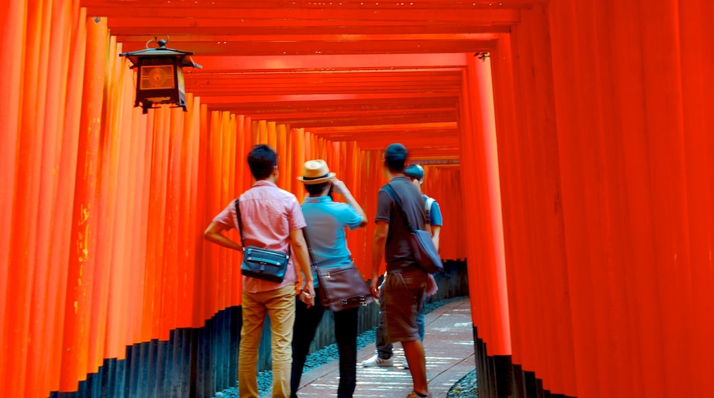Fushimi Inari Shrine featuring a temple or place of worship and interior views as well as a small group of people