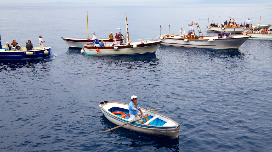Blue Grotto featuring a bay or harbour and boating as well as a large group of people