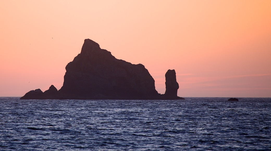 Rialto Beach which includes a sunset, island views and rugged coastline